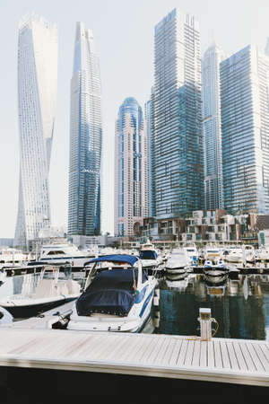Dubai; UAE - June 6, 2020: Dubai Marina promenade with skyscrapers and luxury yachts and boats early in the morning