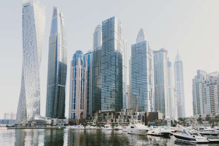 Dubai; UAE - June 6, 2020: Cityscape view over Dubai Marina early in the morning. Residential area with hotels, offices, cafes, restaurants, boats and yachts