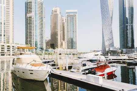 Dubai; UAE - June 6, 2020: Luxury yachts and boats at Dubai Marina early in the morning. Residential area and popular tourist destination in Dubai
