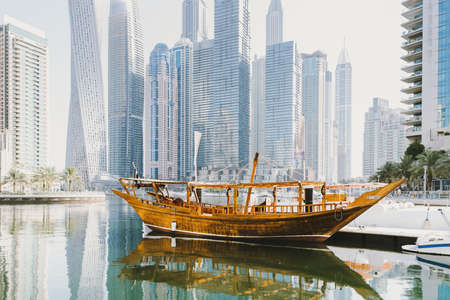Dubai; UAE - June 6, 2020: Traditional Arabic Dhow boat standing at pier at Dubai Marina, a popular city promenade with artificial water canal, skyscrapers, boats and yachts