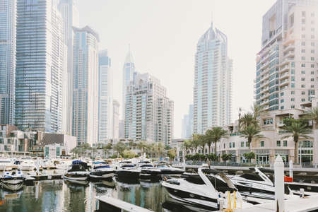 Dubai; UAE - June 6, 2020: Dubai Marina promenade with residential buildings, offices, hotels, yachts and boats early in the morning