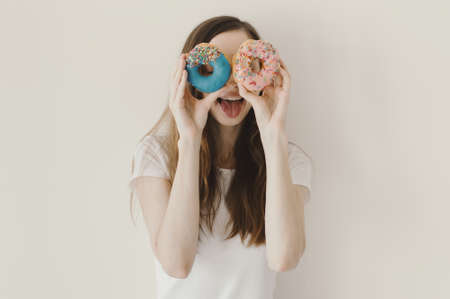 Funny portrait of a woman holding blue and pink donuts near her eyes and showing a tongue