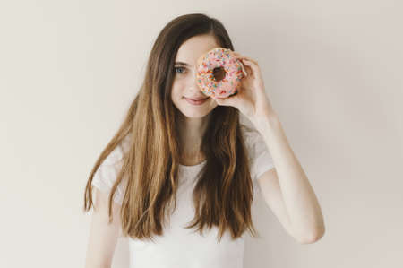 Young European woman holding a ring shaped pink donut near her eye and smiling. Pastry and dessert food Stok Fotoğraf