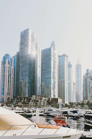 Dubai; UAE - June 6, 2020: Skyscrapers, yachts and boats at Dubai Marina. City view through artificial water canal