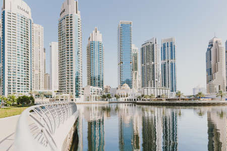 Dubai; UAE - June 6, 2020: View over artificial canal at Dubai Marina promenade. Cityscape with tall residential and office buildings, hotels and mosque