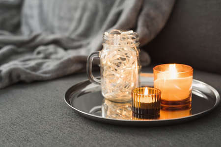 Decorative lights in a glass jar and burning aroma candles on a metal tray. Home decor for cozy atmosphere