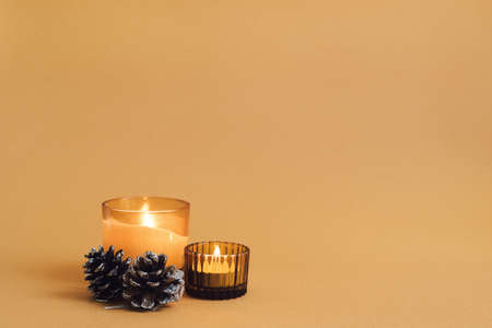 Two burning aroma candles and pine cones on orange background. Minimal style