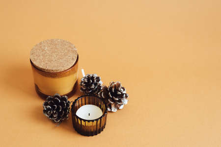 Two aroma candles and decorative pine cones on orange background