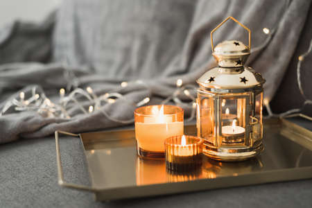 Metal lantern and burning candles on a golden metal tray. Eid al Adha celebration. Muslim holiday atmosphere