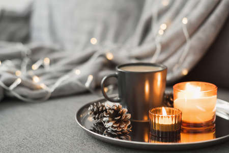 Two burning aroma candles, coffee in a black mug and decorative pine cones served on a round metal tray. Cozy atmosphere. Hygge concept 版權商用圖片