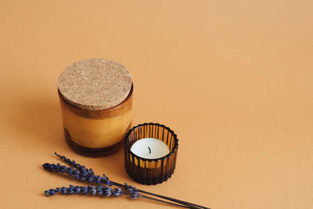 Two aroma candles with ginger scent and dried lavender flower on orange background. Aromatherapy concept 版權商用圖片