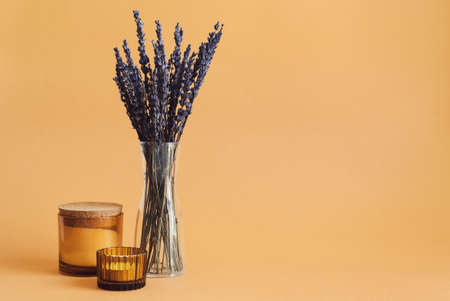 Dried lavender and aroma candles on orange background. Aromatherapy concept