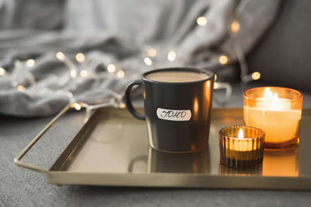 Coffee in black mug served on a metal tray with burning aroma candles, christmas lights as background. JOMO concept. Joy of Missing Out 版權商用圖片