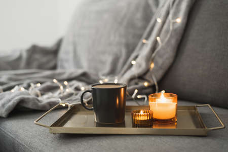 Hot coffee and two burning aroma candles on a metal tray, cozy atmosphere at home