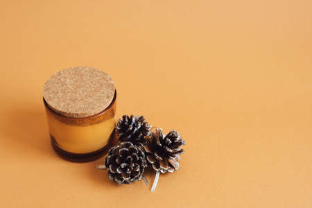 Aroma candle with ginger scent and decorative pine cones on orange background. Autumn - Winter season