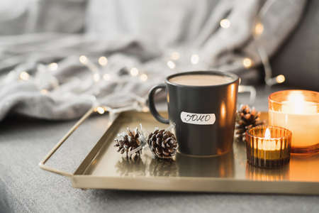 JOMO or Joy of Missing out concept. Coffee in black mug served on a metal tray with two burning candles and decorative pine cones