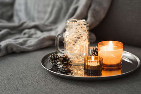 Living room decor: two burning aroma candles of orange color, pine cones and christmas lights in a glass jar. Hygge concept. Autumn - Winter season