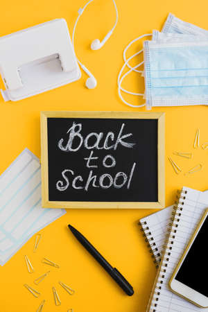 Back to school vertical flat lay. Chalk board, medical face masks, smartphone and school stationery on yellow background