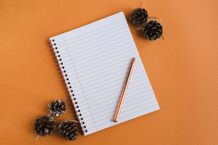 Notebook with empty pages, pen and decorative pine cones on orange background, flat lay. Winter season