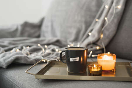 Metal tray with coffee and two burning aroma candles served on a gray sofa, decorative lights. Hygge - danish concept of