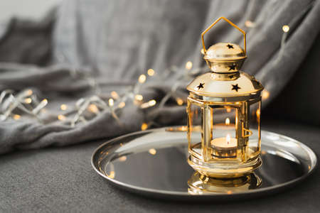 Golden lantern with burning candle on a metal tray. Festive home decor for Eid al Adha or Ramadan holidays