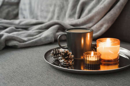 Aroma candles of orange color, coffee in a black mug and decorative pine cones served on a metal tray. Autumn or winter atmosphere Stok Fotoğraf