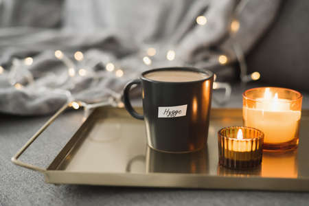 Hygge concept: hot coffee in black mug served on a metal tray with two burning candles, decorative lights as background. Cozy atmosphere