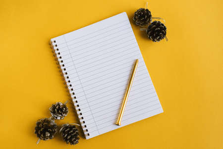 Notebook with clean pages, metal pen and decorative pine cones on yellow background, top view