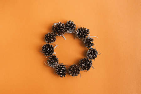 Pine cones round frame on orange background, flat lay, top view. Pine cones wreath