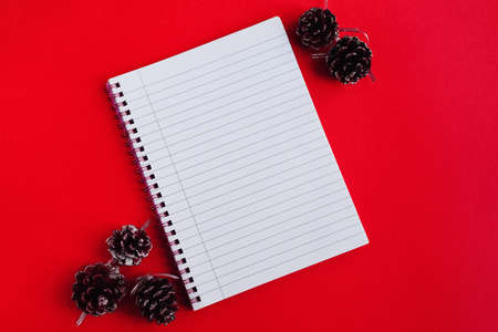 Notebook with empty pages and decorative pine cones on red background, top view