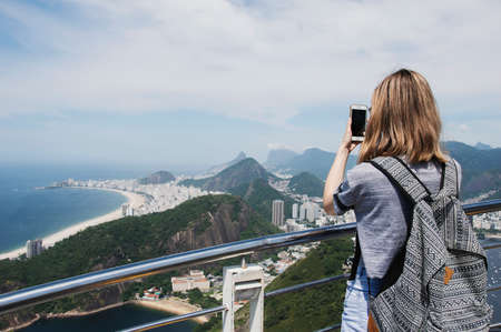 Rio de Janeiro; Brazil - February, 12, 2019: Female tourist taking a mobile photo of Copacabana beach from the observatory deck at Sugarloaf mountain in Rio