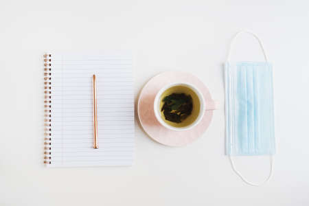 Medical face mask, green tea in a pink cup and notebook with a metal pen on white table, flat lay