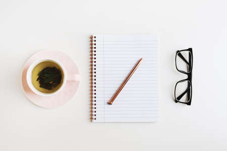 Simple feminine flat lay with green tea in a pink cup, notebook with metal pen and reading glasses