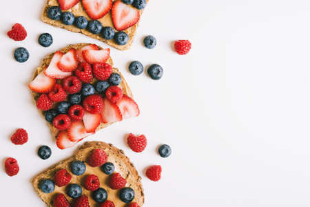 Breakfast toasts with wholegrain bread, peanut butter, strawberry, blueberry and raspberry on white table, top view. Healthy breakfast