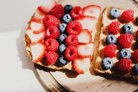 Two peanut butter toasts with raspberry, blueberry and strawberry on wooden board captured in early morning sunlight