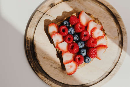 Peanut butter toast with whole grain bread and fresh seasonal berries on wooden cutting board  captured early in the morning. Healthy breakfast food