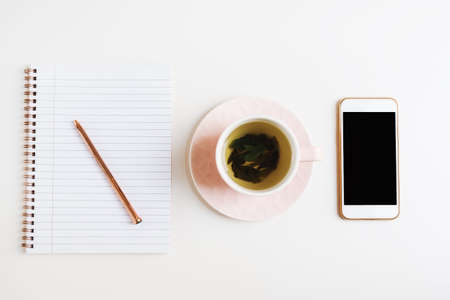Green tea in a pink cup, mobile phone and notebook with metal pen on white office desk, top view. Freelance concept, flat lay