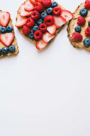 Vertical background with peanut butter toasts with seasonal berries. Brown bread with creamy spread, strawberry, blueberry and raspberry on white table. Healthy snack