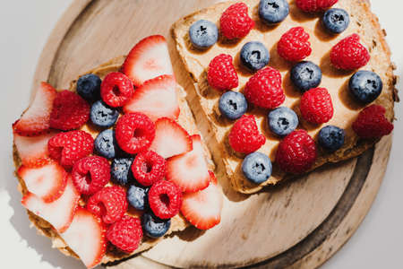 Two whole grain bread toast with peanut butter, fresh blueberry, raspberry and strawberry on wooden cutting board, top view. Breakfast toast with healthy topping