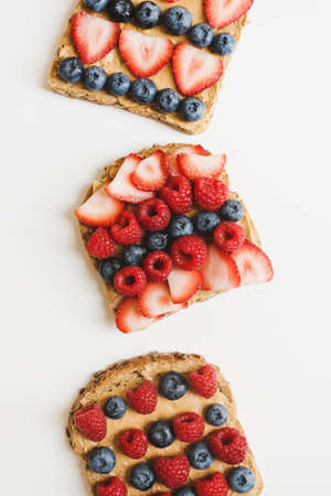 Peanut butter toasts with fresh seasonal berries. Whole grain bread with creamy spread, strawberry, blueberry and raspberry on white table, top view