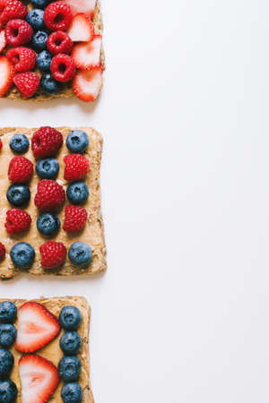 Breakfast toasts with whole grain bread, peanut butter, raspberry, strawberry and blueberry on white background, top view, space for text