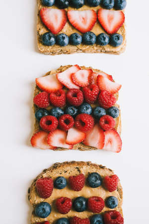 Three peanut butter toasts with fresh berries. Whole meal brown bread with creamy spread, blueberry, raspberry and strawberry topping