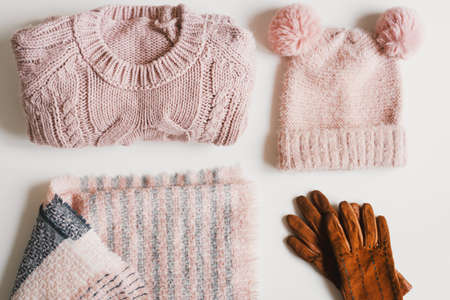 Pink knitted hat with funny pompoms, handmade sweater, woolen scarf and suede gloves on white background. Winter wardrobe flat lay. Warm clothing