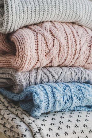 Pile of knitted woolen sweaters. Warm clothes for fall and winter season. Knitwear storage and care
