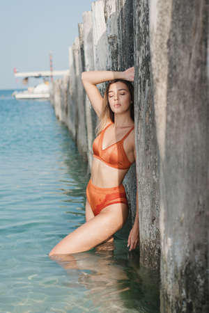 Young woman in bikini of orange color standing in clear water at the beach near wooden pier and sunbathing