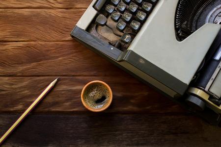 maquina de escribir: m�quina de escribir vieja con el caf� y el l�piz sobre la textura de madera vieja Foto de archivo