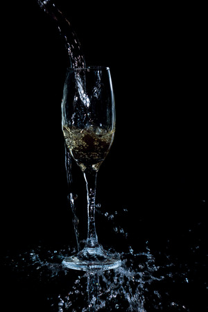 abstract liquor: white wine pouring on black background Stock Photo