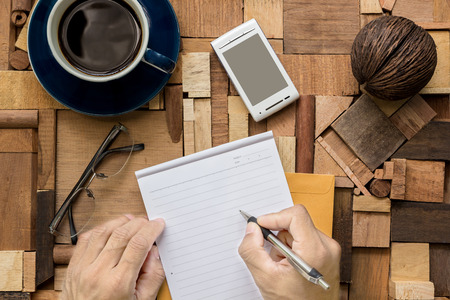 blank sheet: Writing on blank sheet of paper on wood texture table