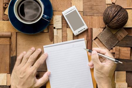 hoja en blanco: Escribir en la hoja de papel en blanco sobre la mesa de madera de textura