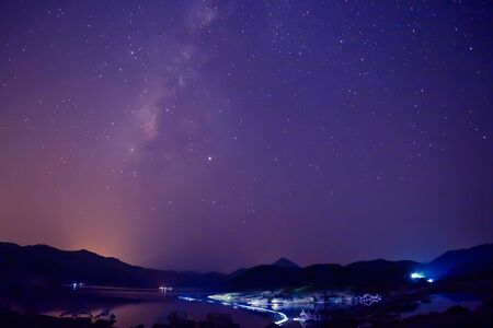 Night photos include the Milky Way, mountains, bamboo rafts on the river. And there is a light from a fishing boat. 版權商用圖片